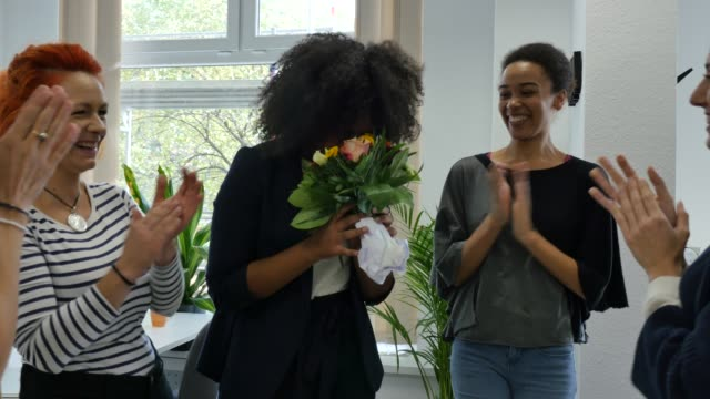 Businesswoman giving bouquet to smiling colleague