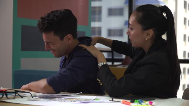 vídeos de stock e filmes b-roll de businesswoman giving massaging to his male colleague in office - dor no pescoço
