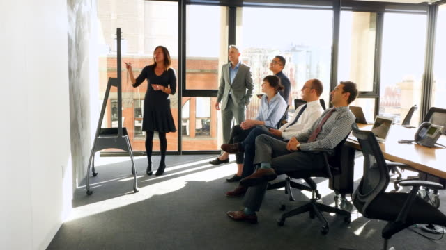 ms ts businesswoman giving presentation at whiteboard to colleagues in conference room - whiteboard stock videos and b-roll footage