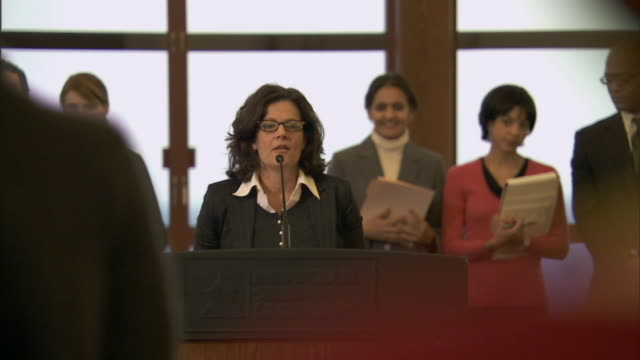 MS businesswoman giving speech at lectern as staff stands behind her/ Montclair, New Jersey