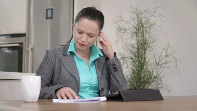 hd dolly: businesswoman going over paperwork in the morning - hot desking bildbanksvideor och videomaterial från bakom kulisserna