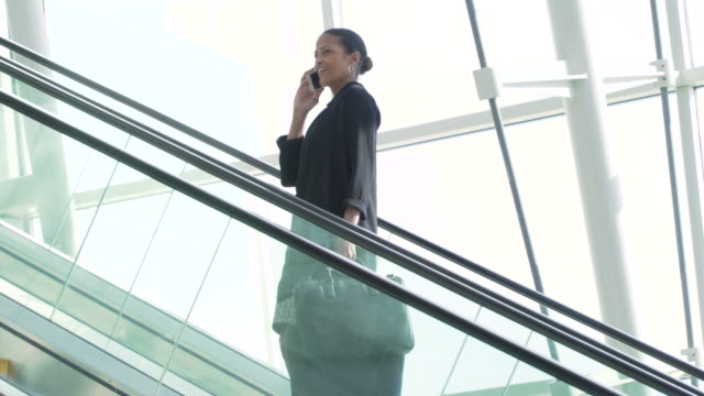 businesswoman going up escalator and talking on mobile phone - escalator stock videos & royalty-free footage