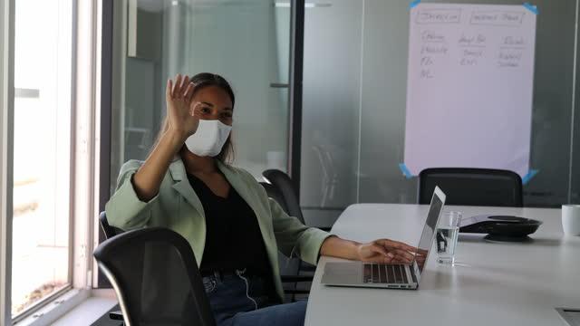 vidéos et rushes de collègue d'accueil de femme d'affaires pendant un appel vidéo dans le bureau - saluer de la main