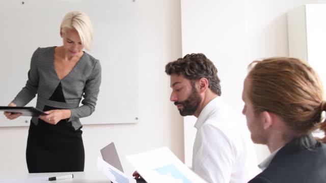 実業家のオフィスで 2 人の男性同僚に書類を渡す - 渡す点の映像素材/bロール