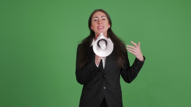 businesswoman happily speaks by a megaphone on a green background - megaphone stock videos & royalty-free footage