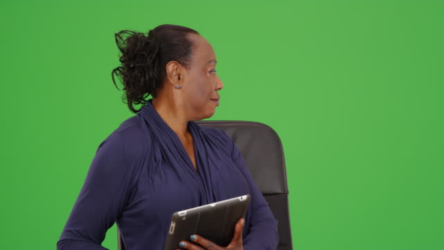 businesswoman happily uses her tablet while posing for portrait on green screen - maestra video stock e b–roll