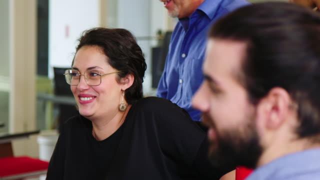 vidéos et rushes de femme d'affaires ayant une discussion occasionnelle avec des collègues - partenariat