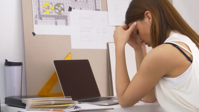 Geschäftsfrau, die mit Kopfschmerzen im Büro