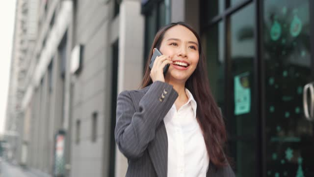 businesswoman having business talk on mobile phone in front of office building - business talk stock videos & royalty-free footage