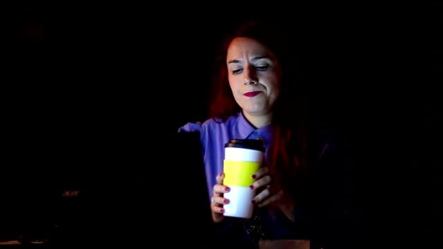 Geschäftsfrau mit Kaffeepause in dunklen Büro