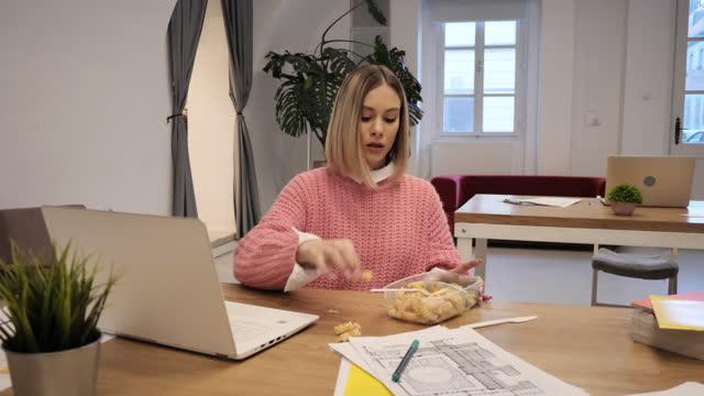 vidéos et rushes de femme d'affaires ayant des méfaits dans le bureau tout en mangeant le déjeuner - 18 23 mois