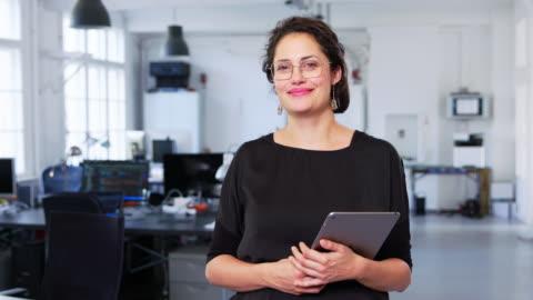 affärskvinna som innehar en digital surfplatta i tjänst - nystartat företag bildbanksvideor och videomaterial från bakom kulisserna