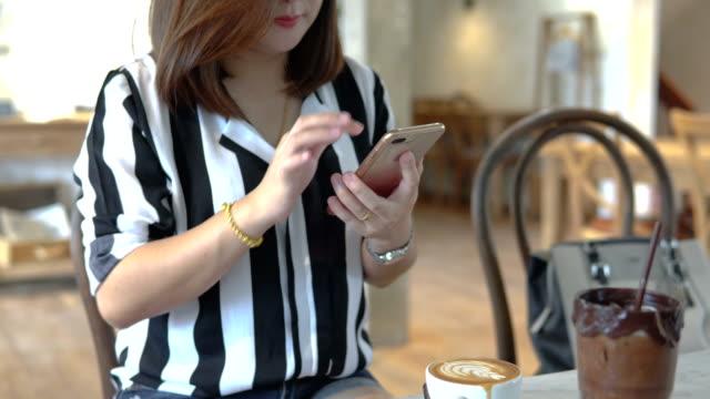 vídeos de stock, filmes e b-roll de empresária, segurando o copo de café usando telefone inteligente na mesa na loja de café. - smart