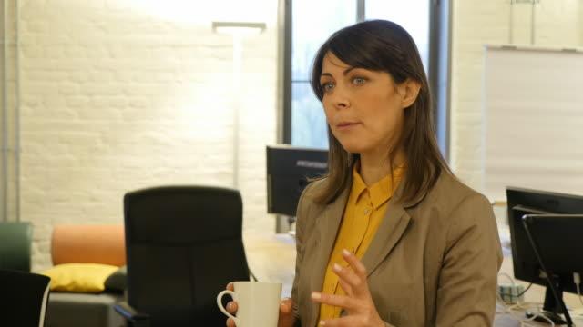 Businesswoman holding coffee mug while explaining