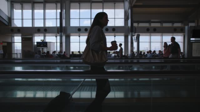 vídeos y material grabado en eventos de stock de slo mo. businesswoman holding coffee travels along moving walkway through airport termial. - sala de embarque del aeropuerto