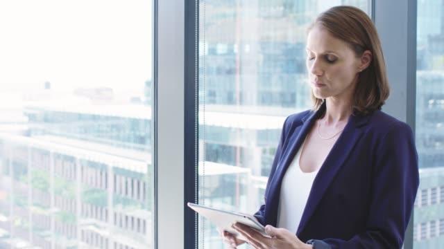Businesswoman holding digital tablet by window