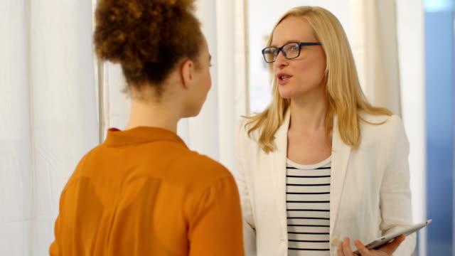 Zakenvrouw digitale tablet tijdens een gesprek met collega bedrijf
