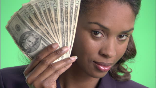 ecu, businesswoman holding fan of american dollar banknotes in front of face in studio, portrait - corruption stock videos and b-roll footage