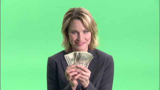 vídeos de stock e filmes b-roll de cu, businesswoman holding fan of american dollar banknotes in studio, portrait - nota de dólar dos estados unidos