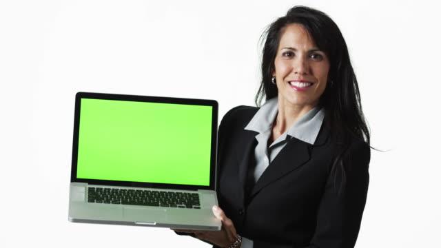 ms businesswoman holding laptop, against white background / orem, utah, usa - weibliche angestellte stock-videos und b-roll-filmmaterial