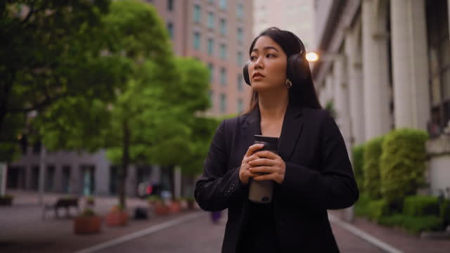 businesswoman holding reusable mug and walking in street while listening to music - looking away stock videos & royalty-free footage