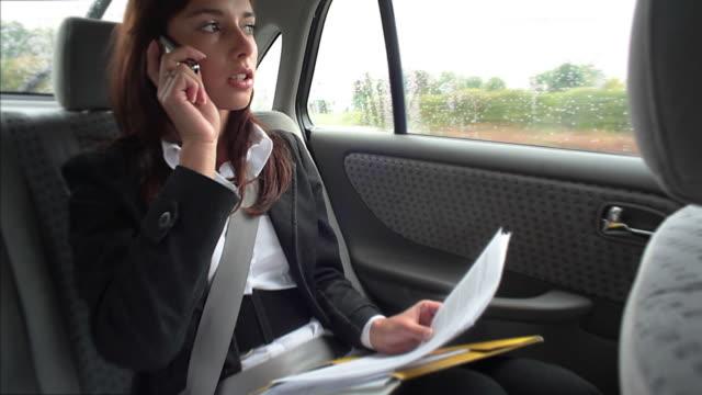 vidéos et rushes de femme d'affaires dans une voiture - siège arrière de passager