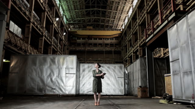 Businesswoman in a warehouse, zoom in