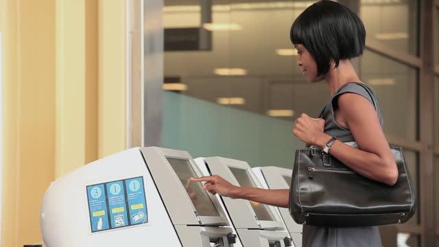 businesswoman in airport getting ticket at kiosk - kiosk stock-videos und b-roll-filmmaterial