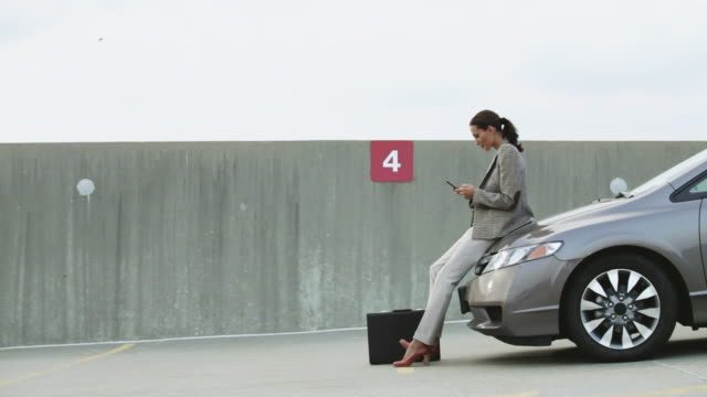 businesswoman in car park, texting on mobile phone - lehnend stock-videos und b-roll-filmmaterial