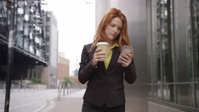 Businesswoman in city using smart phone with takeaway coffee