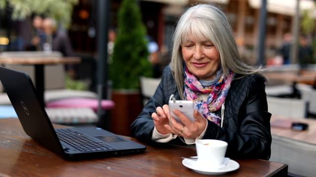 vidéos et rushes de femme d'affaires dans le café-restaurant à l'aide de smartphone - adulte d'âge mûr
