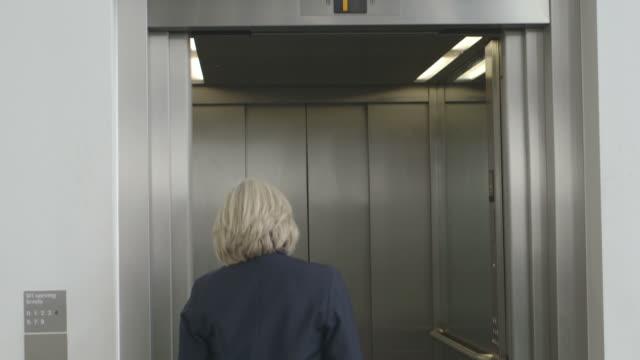 businesswoman in elevator - solo una donna matura video stock e b–roll