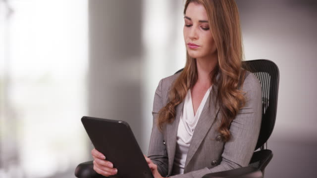Businesswoman in her 20s using tablet while sitting on her chair
