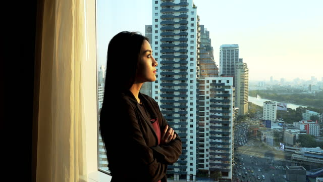 Geschäftsfrau in ihrem Büro, schaut aus dem Fenster.