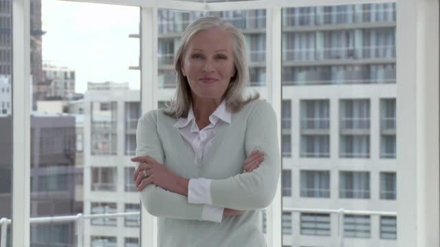 businesswoman in office crossing arms, portrait - solo una donna matura video stock e b–roll