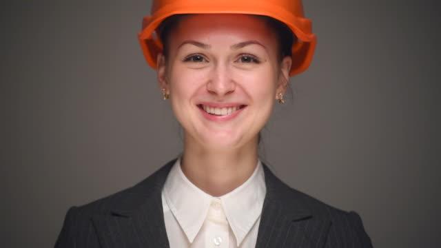 vídeos de stock e filmes b-roll de mulher de negócios em laranja capacete de proteção - capacete de desporto