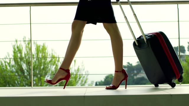 businesswoman in red highheels arriving to a luxurious spa hotel - mini skirt stock videos & royalty-free footage