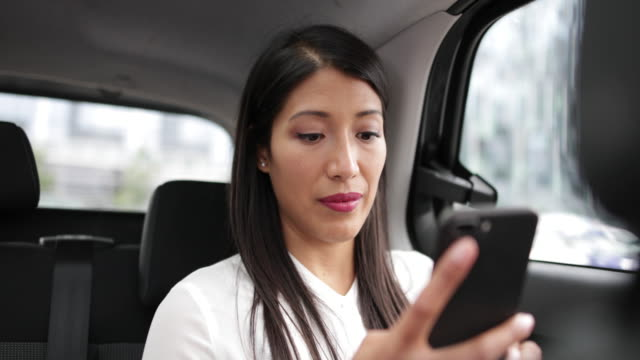 vidéos et rushes de businesswoman in taxi cab using smartphone - taxi