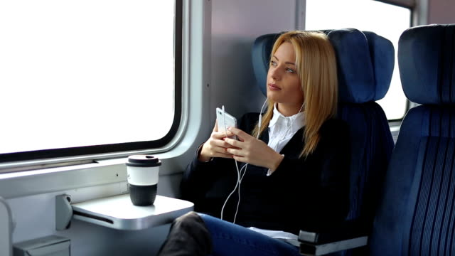 Businesswoman in train listening music