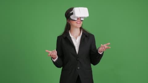 vídeos y material grabado en eventos de stock de empresaria en gafas de realidad virtual sobre un fondo verde - simulador de realidad virtual
