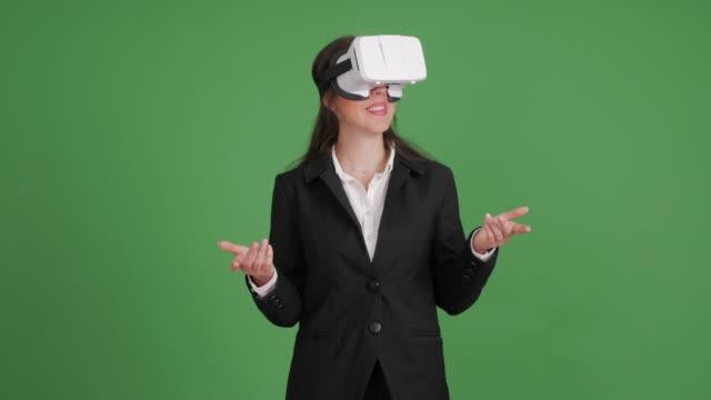 vídeos de stock e filmes b-roll de businesswoman in virtual reality glasses on a green background - simulador realidade virtual
