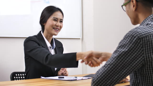 Businesswoman Interviewing Man Job Applicant In Office