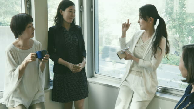 businesswoman is leading informal meeting with colleagues at office corner - ビジネスウーマン点の映像素材/bロール
