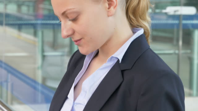 vídeos de stock e filmes b-roll de businesswoman is looking at mobile phone in train station. - trabalhadora de colarinho branco