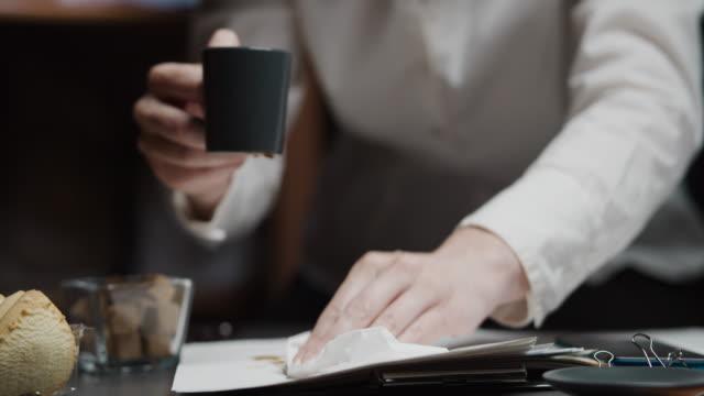 vídeos y material grabado en eventos de stock de empresaria está desbordando café durante el trabajo de papel - derramar actividad