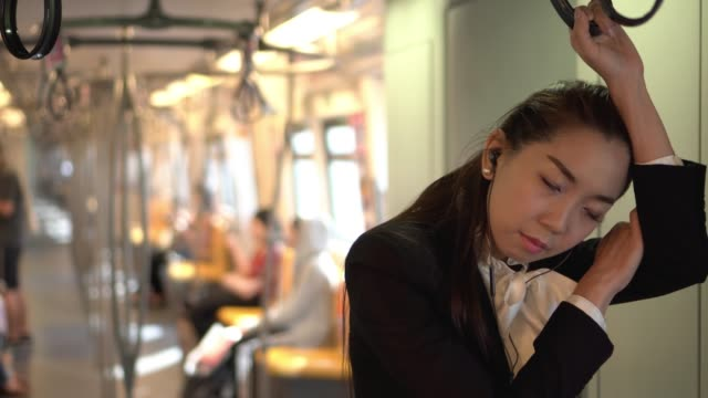 businesswoman is standing and sleeping in train - napping stock videos & royalty-free footage