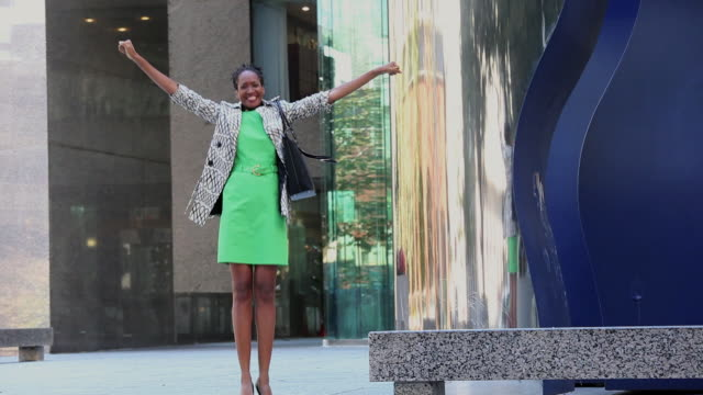 ms zo businesswoman jumping and celebrating in front of office building / richmond, virginia, united states - promotion employment stock videos & royalty-free footage