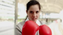 Businesswoman keeps punching and raising hands with red boxing gloves