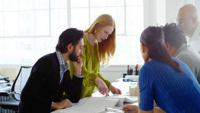 MS businesswoman leading project discussion with group of coworkers at office conference room table