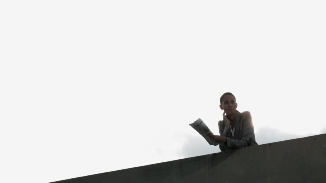 businesswoman leaning over wall with newspaper, low angle - one mid adult woman only stock videos & royalty-free footage